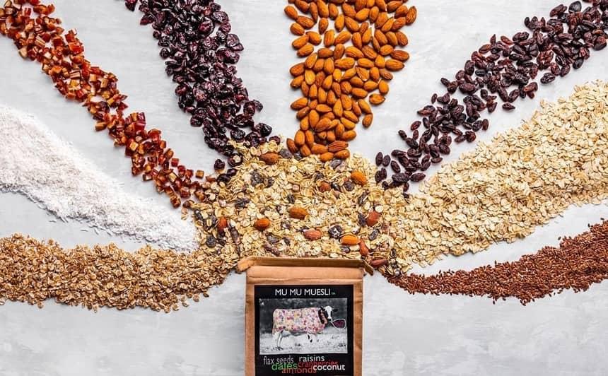 oats, nuts and grains going into a box of mu mu muesli
