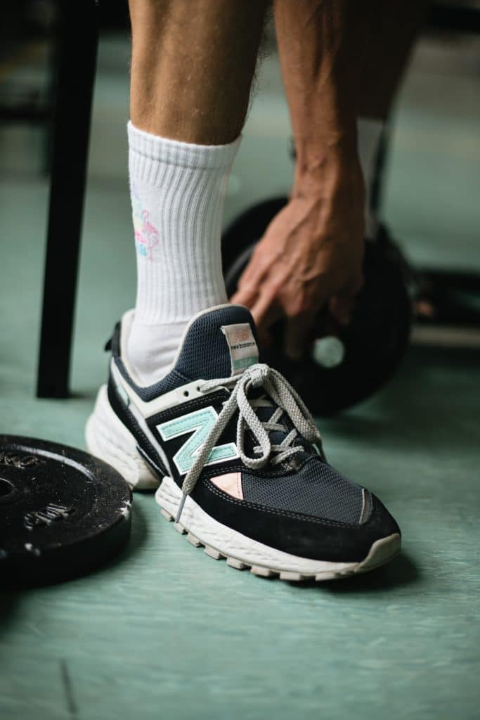 man's sneaker next to weights during a workout