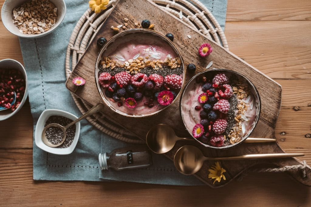 two smoothie bowls on a brown wood background